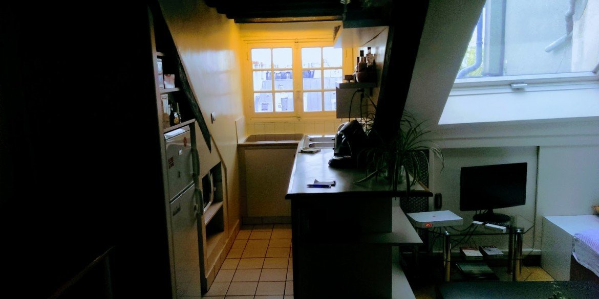 small Paris apartment with glowing yellow window in kitchen