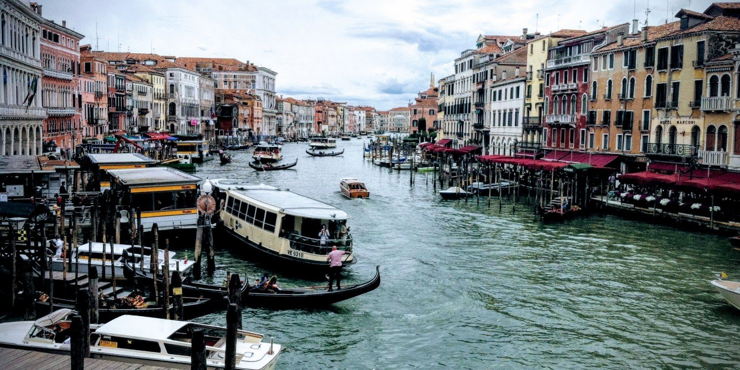 Venice, Italy seen from bridge, with boats, gondolas and buildings overlooking canal