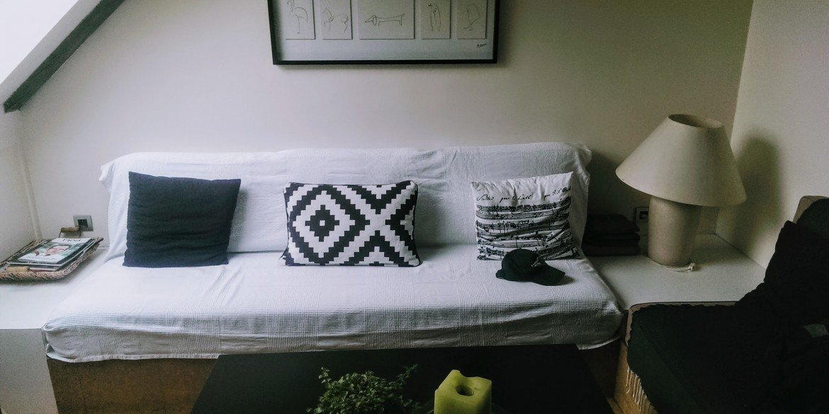 basic sofa with three black and white pillows and small lamp