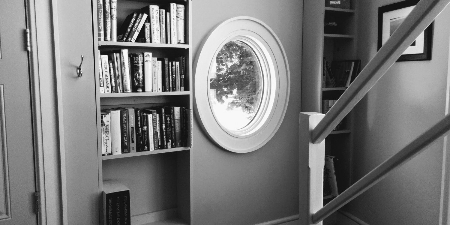 interior of house with porthole window and bookshelves