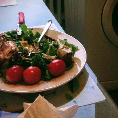 salad with greens, cherry tomatoes and chicken on white plate
