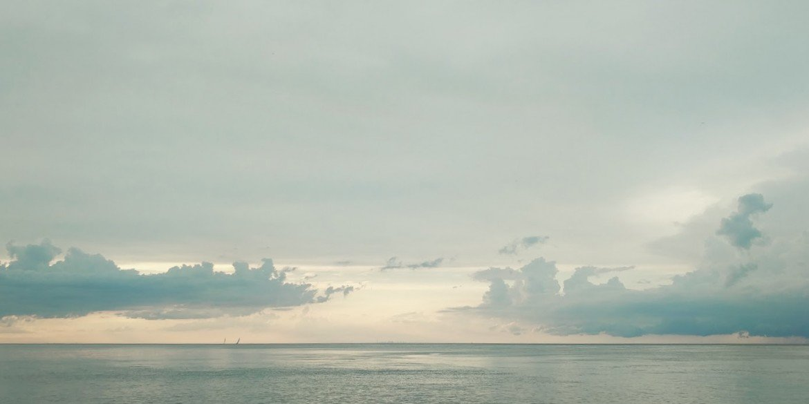 flat ocean with pale green sky