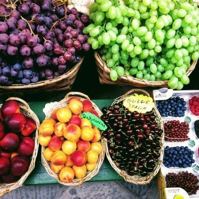 green and purple grapes, cherries, peaches, raspberries, blueberries on display in baskets