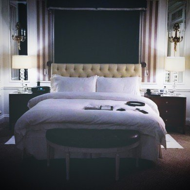 upscale hotel bedroom at night with bed, table lamps and striped wallpaper