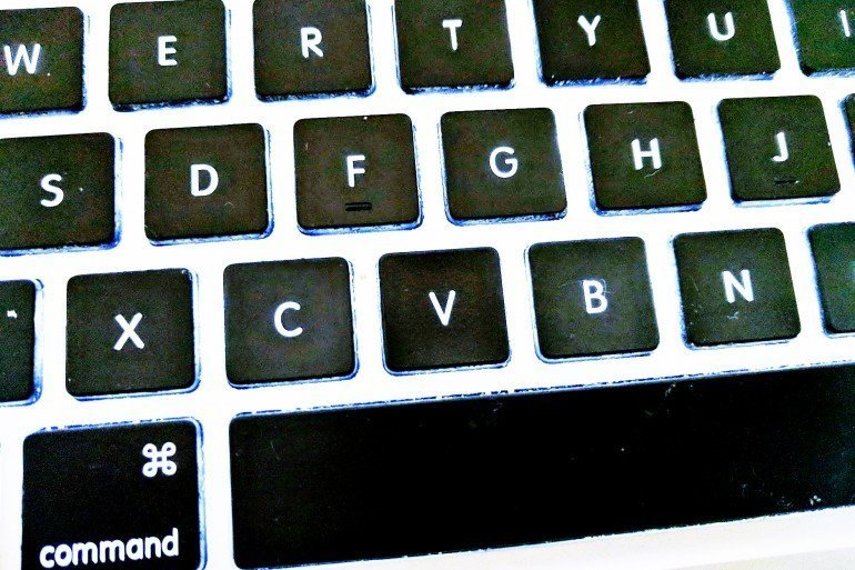 closeup of computer keyboard with black keys and white letters