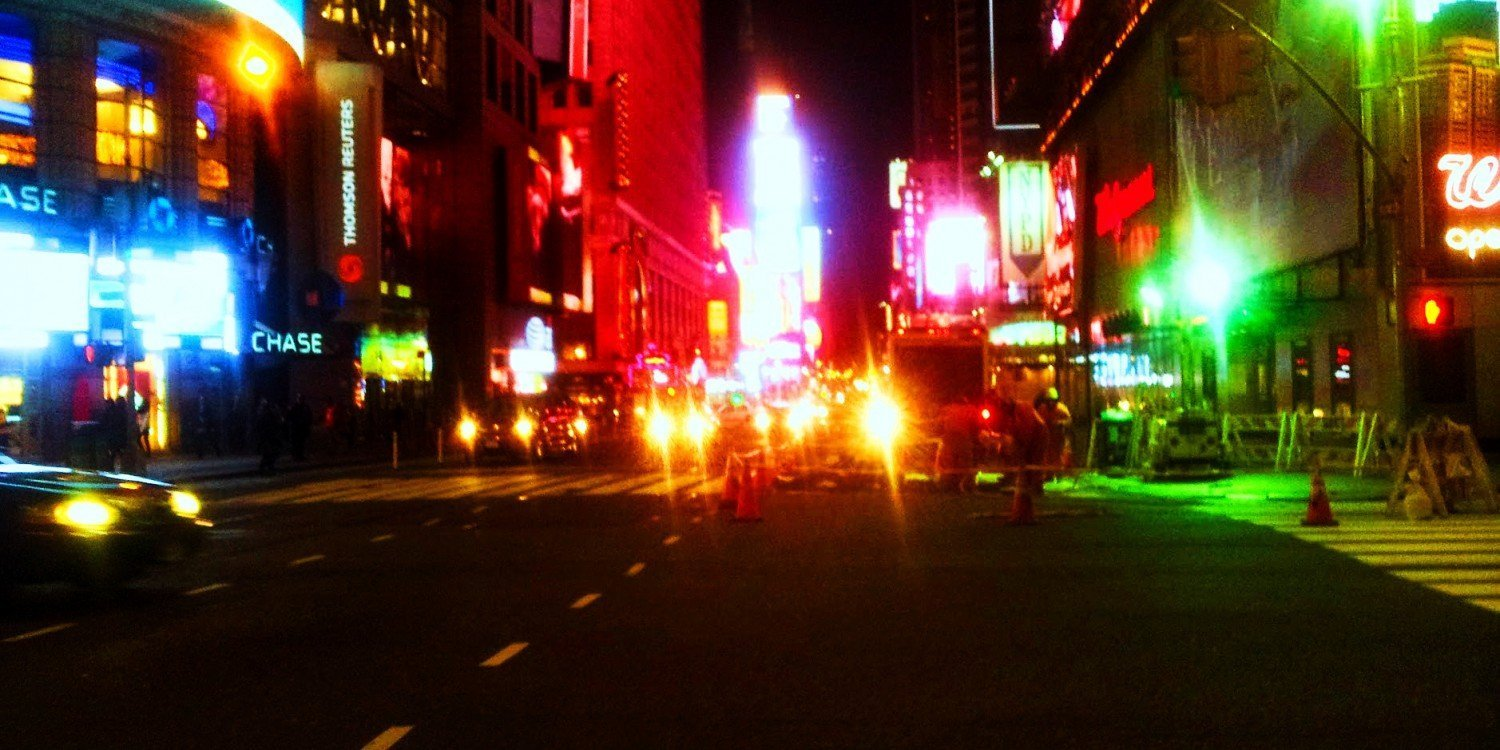 New York City street at night with lights in blue, yellow, red and green