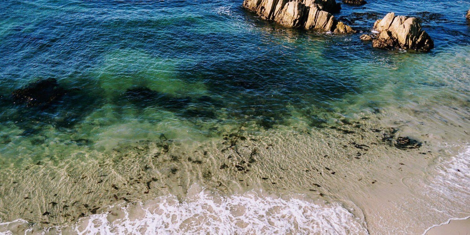 white foamy waves on seashore with rocks and blue green water