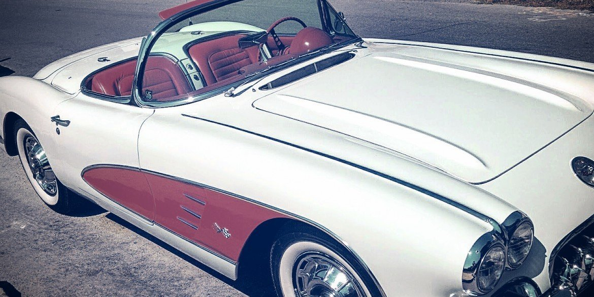 classic red and white two-seater convertible car with top down, parked at roadside