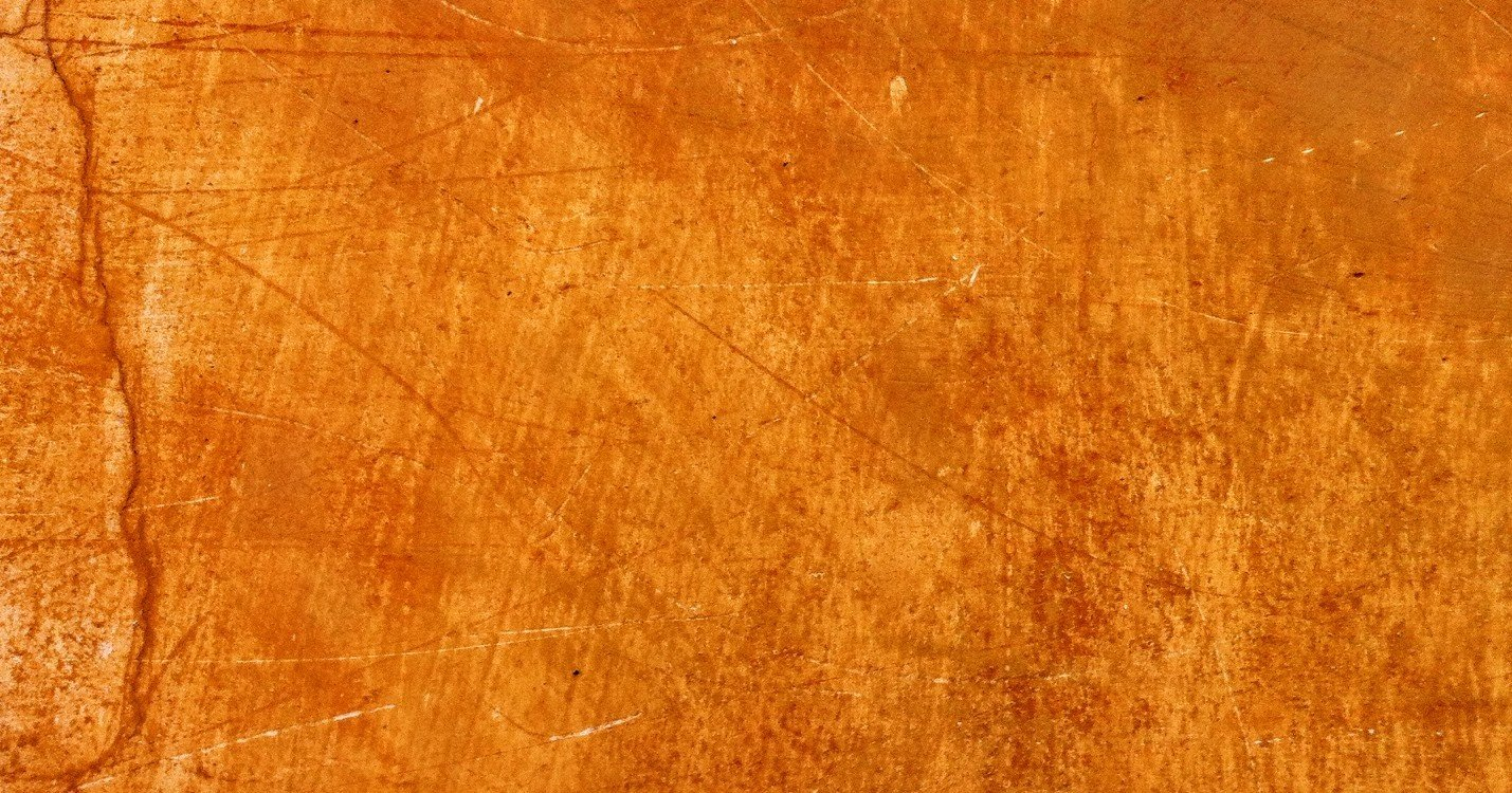 orange cement wall covered in scratches