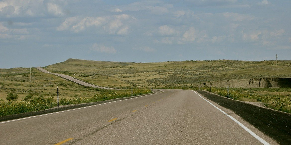 empty paved road winds like ribbon across American midwest