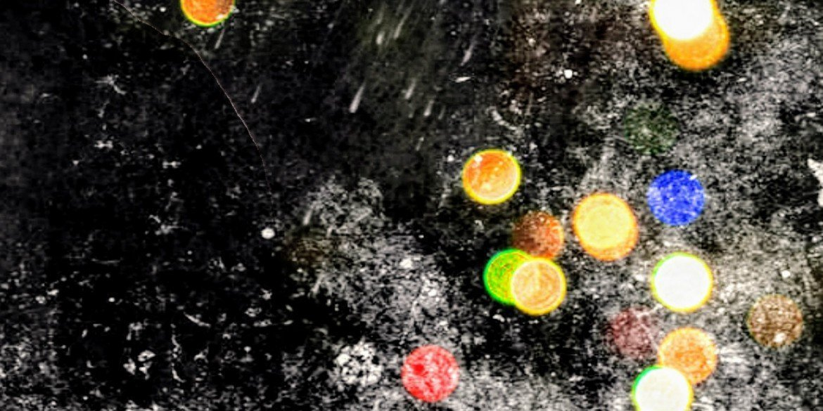 bright colorful circles in yellow, green, red and blue on black surface