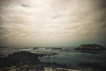 moody ocean view with rocks and low grey sky