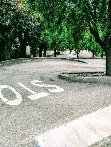 winding road in San Francisco and word, stop, painted in white on pavement