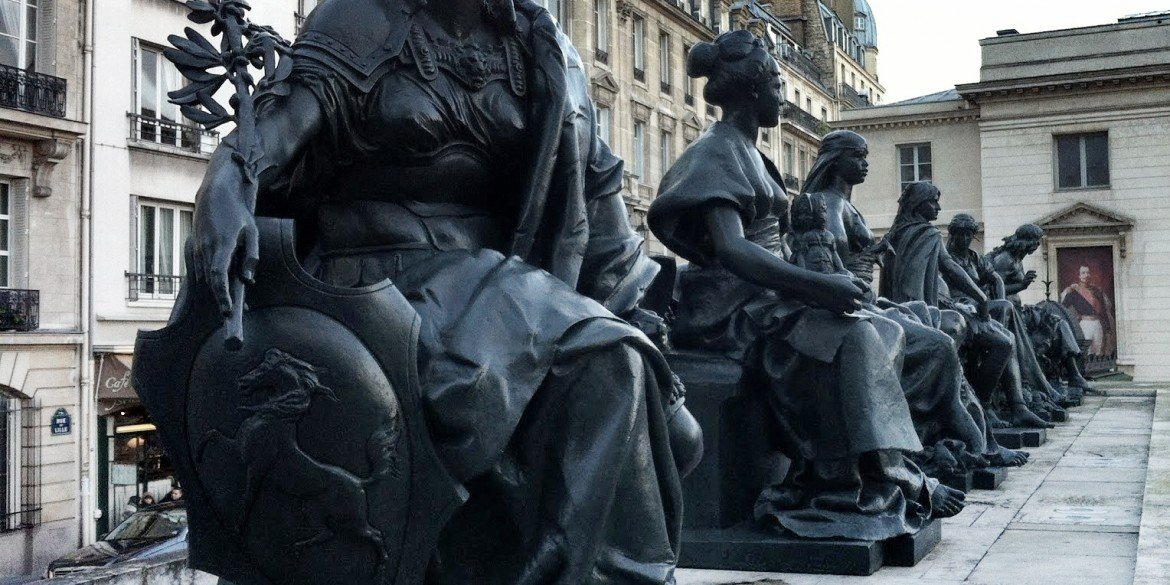 six statues of seated people in a row