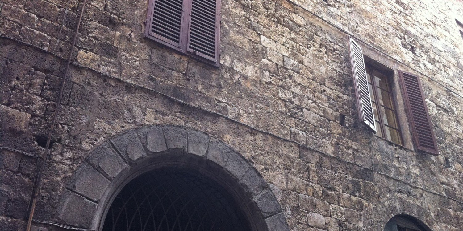 stone wall with archway and shuttered windows