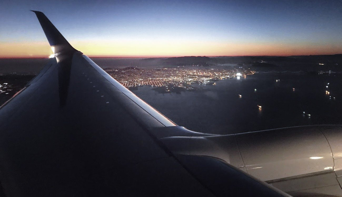 looking out airplane window across wing tip at city lights below