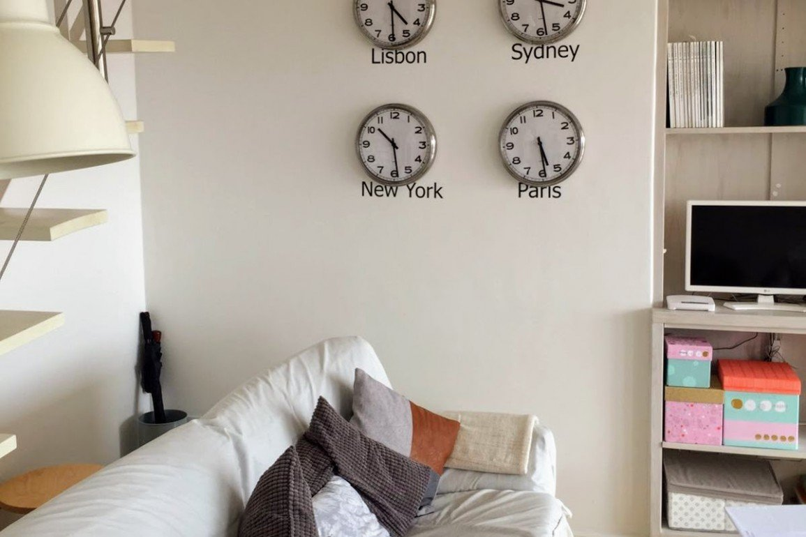 apartment interior with clocks on wall showing time in New York and Paris