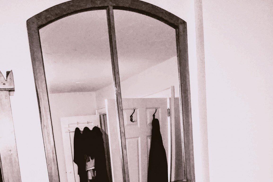 wall mirror reveals clothing on door hooks