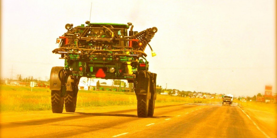 green farm vehicle driving on highway looks like alien creature