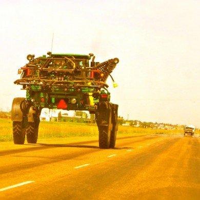 green farm vehicle driving on highway looks like alien creature
