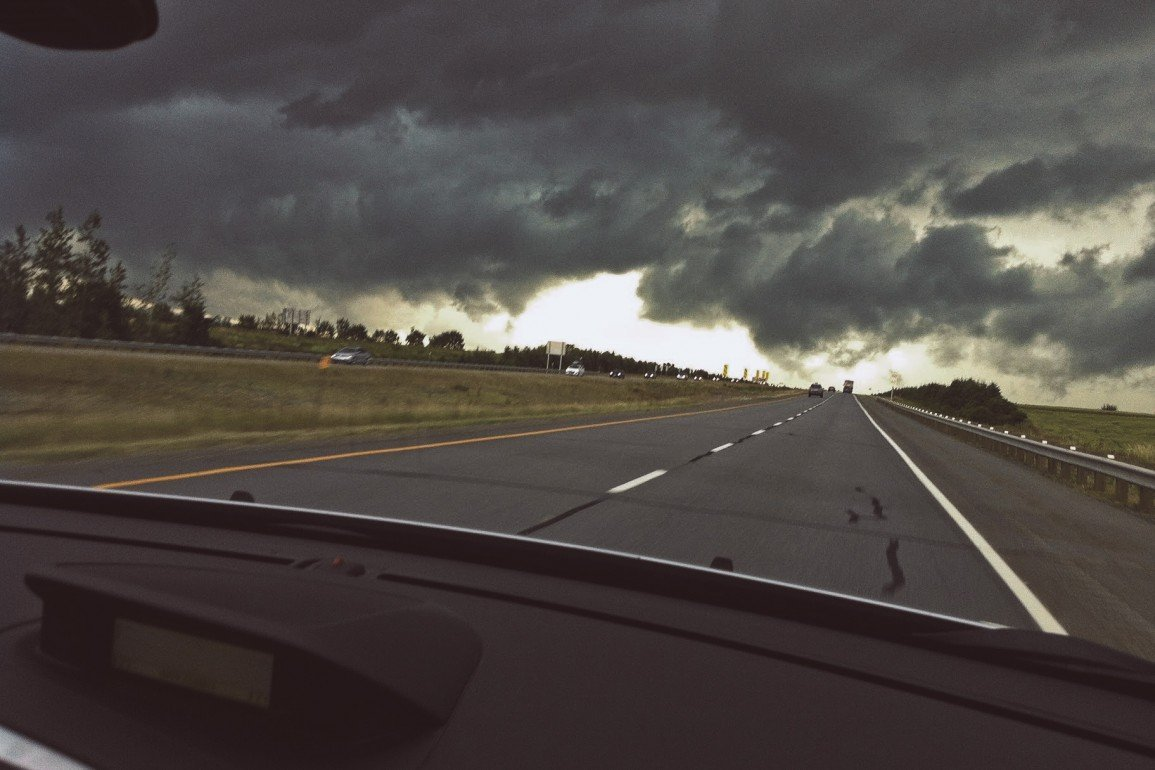 view from passenger seat of moving car on divided highway with dark clouds looming ahead