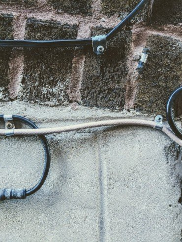TV cable looping in circles on exterior brick wall of house