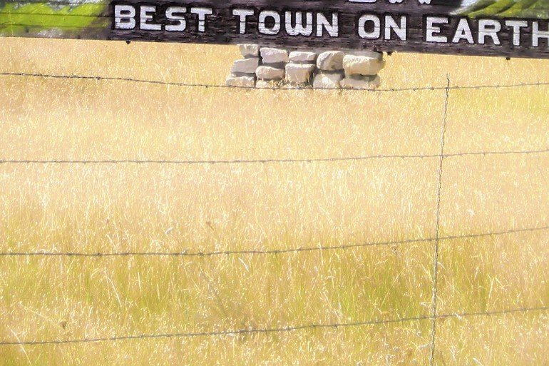 sign in field of grain says, best town on earth, with barbed wire fence in foreground