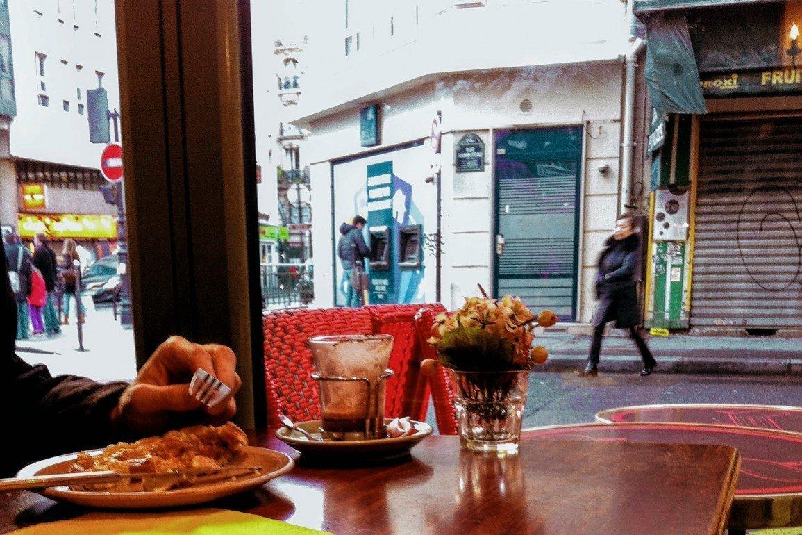 looking out window of cafe in Paris as woman walks by in street