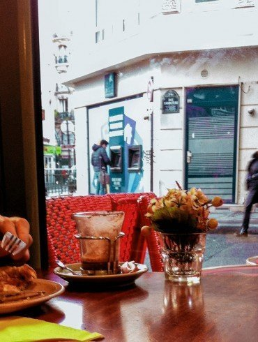 looking out window of cafe in Paris as woman walks by in street
