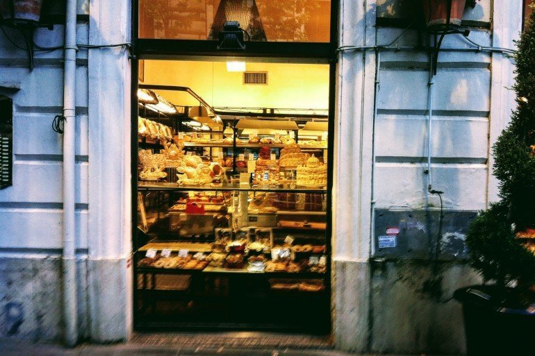 pastries on racks in window of stone walled restaurant
