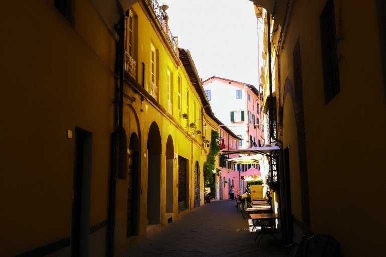 curved lane in Rome with pink and yellow walled buildings