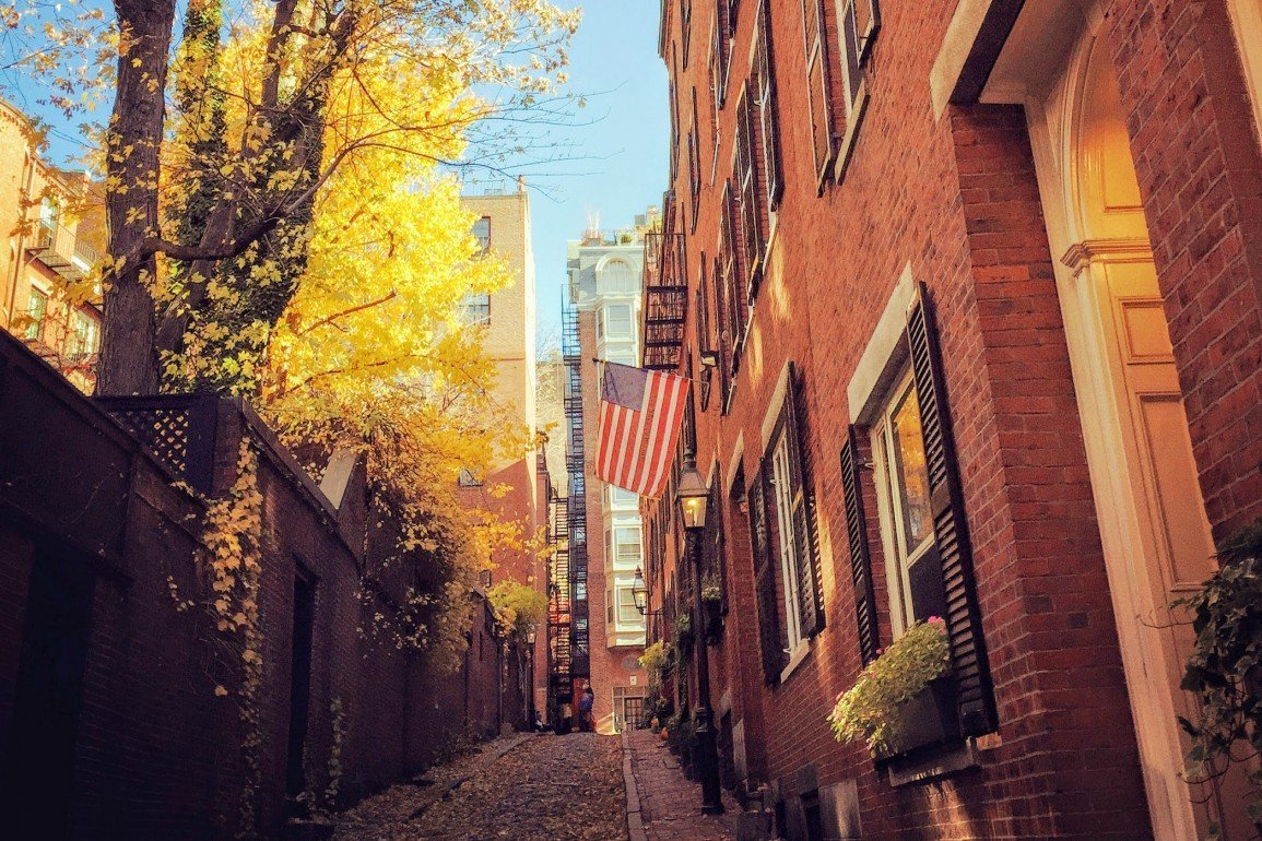 American flag hangs from red brick building with yellow tree across lane