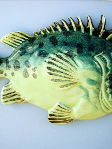 green ceramic fish on pale blue wall