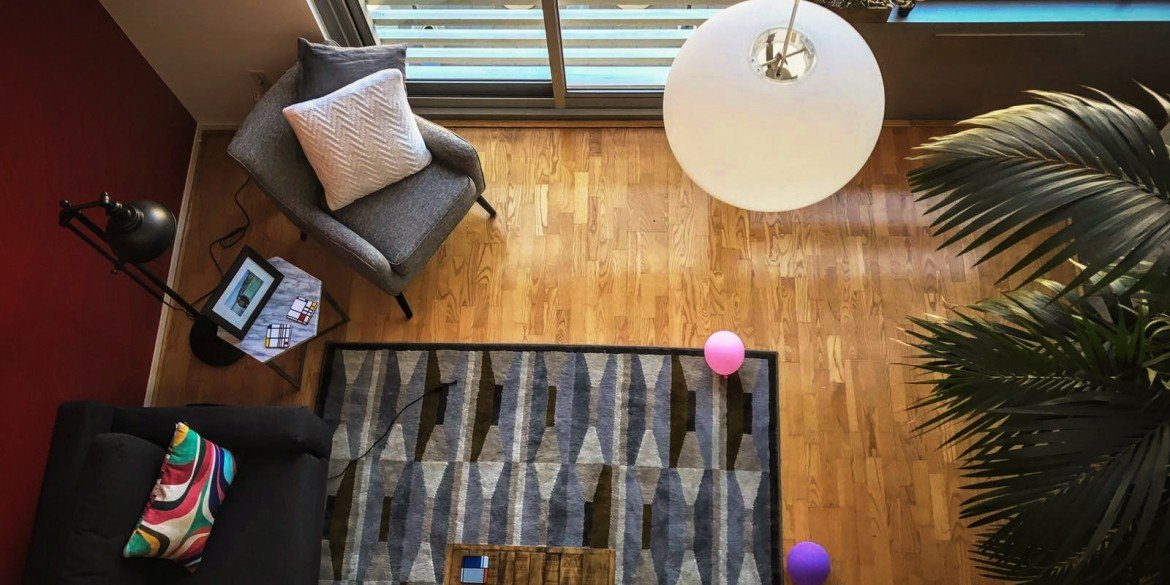 looking down from loft into living room of apartment with balloons on floor