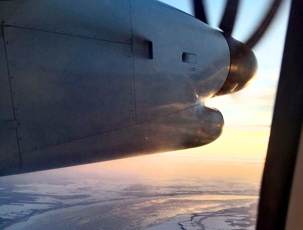 airborne airplane engine with spinning propeller and icy river far below