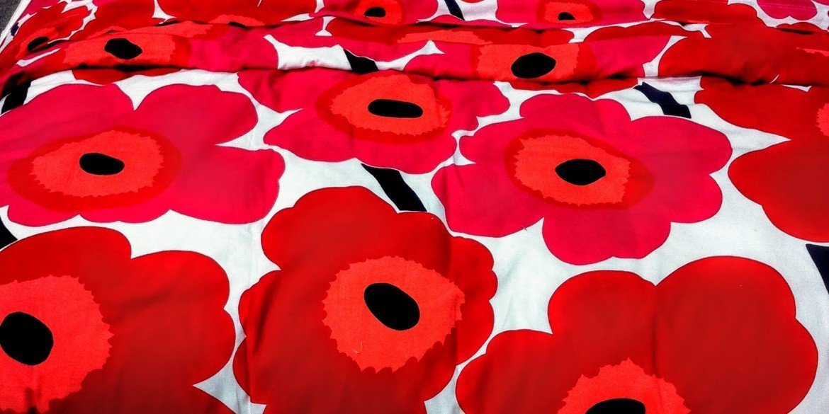 red and black flowers adorn white bed comforter