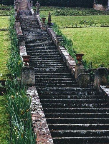 old stone staircase rises through green hillsides