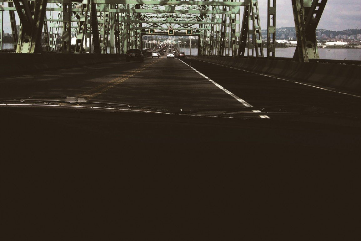 view from passenger seat of car traversing bridge with steel girders