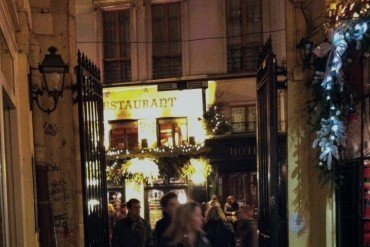 outside a Parisian restaurant at night as people walk through tall iron gate
