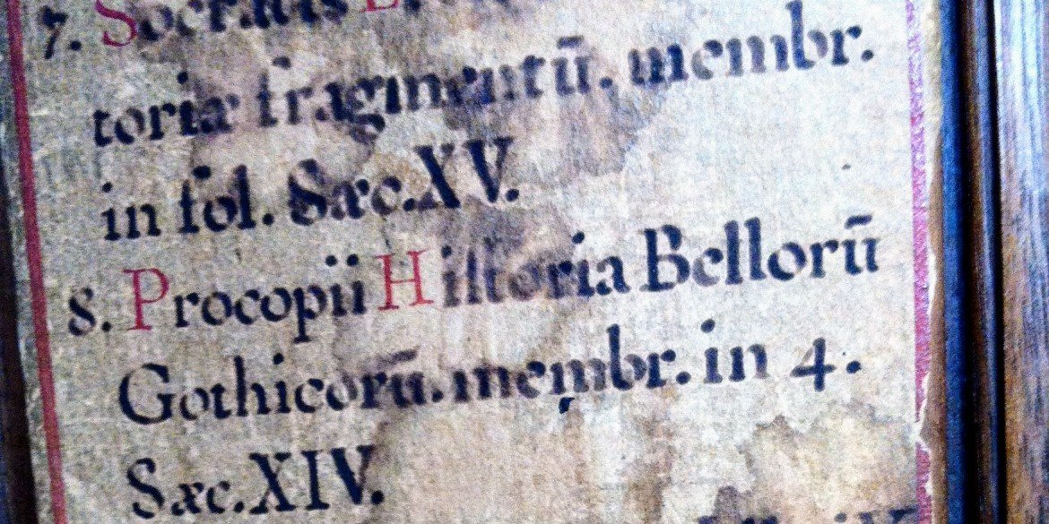 Latin words in black ink on very old stained paper
