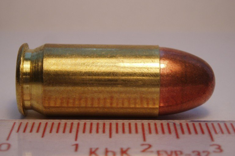 .45 caliber brass cartridge laying beside ruler with red markings