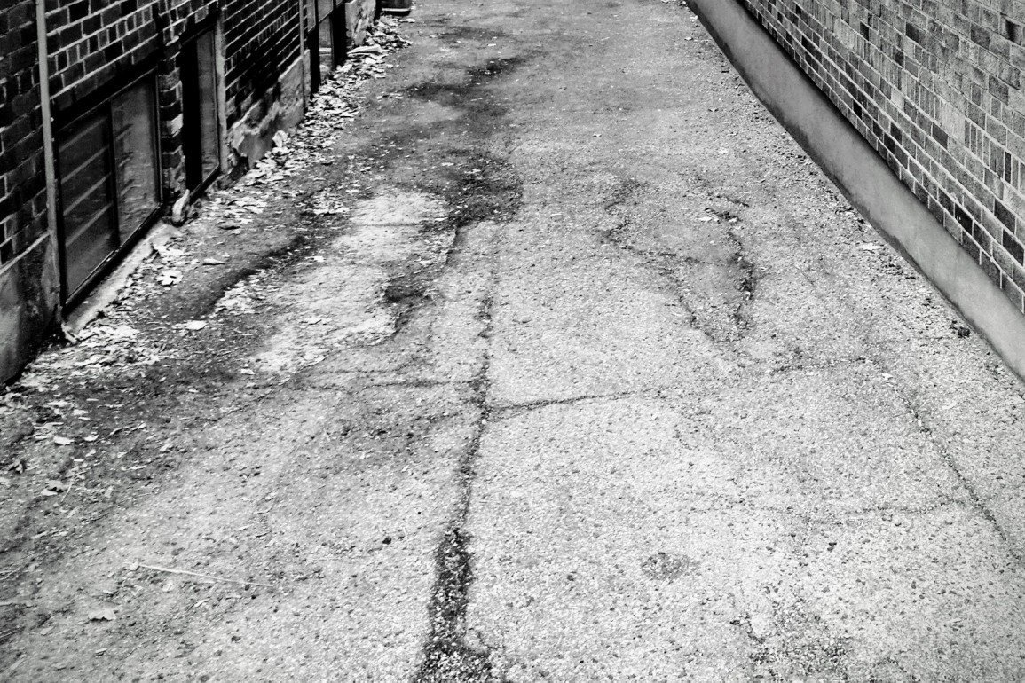 broken pavement in narrow lane between brick walls