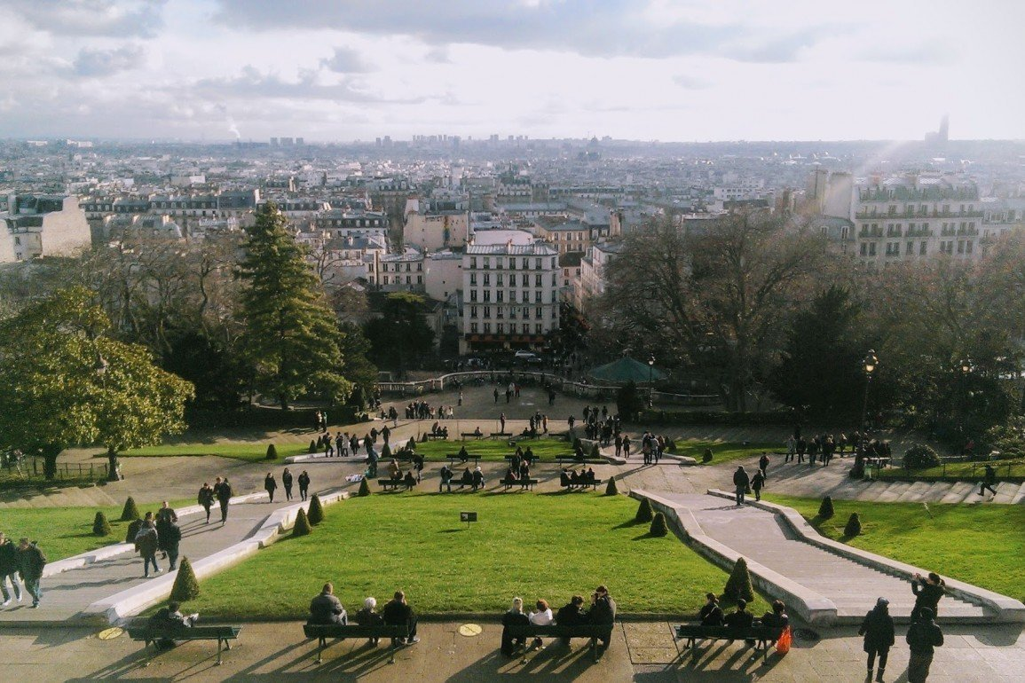 Paris skyline with people enjoying hillside park in foreground