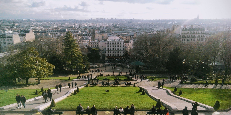 Paris skyline with people enjoying hillside park in foreground