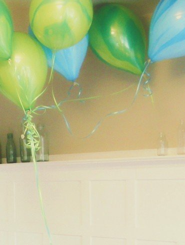 green and blue balloons floating above green glass bottles on white mantel