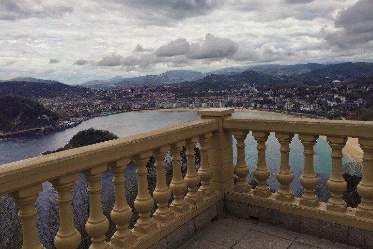 view over stone railed balcony of bay and city far below with mountains beyond