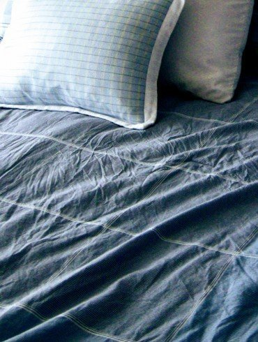 wrinkled sea blue bed sheet and several pillows