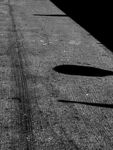 shadows on old black pavement