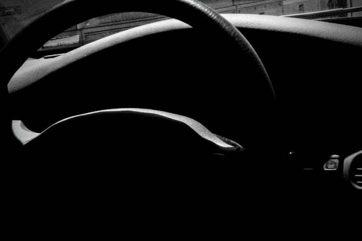 curved steering wheel in dark interior of car