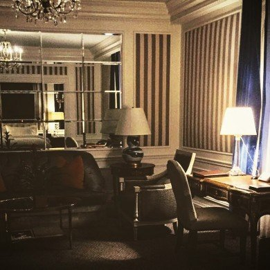 upscale hotel room with writing desk, chairs, sofa, table lamps and mirror on wall